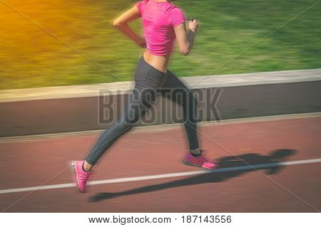 Female jogger running on athletic track. Motion blur.