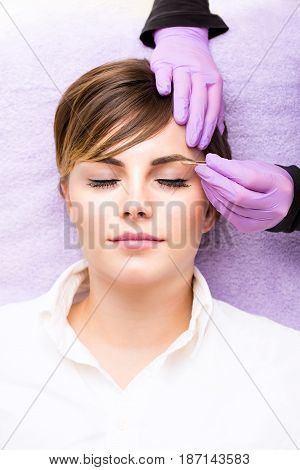 Pretty Young Woman Having Her Eyebrows Plucked