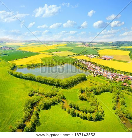Aerial view to rural landscape with Uhlava river and fish pond. Luzany village near Pilsen in Czech Republic. Spring in Central Europe.