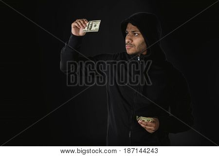 Young African American Robber In Zoodie Holding Money Isolated On Black