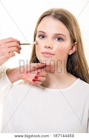 Beautician Applying A Cream Blush To A Young Woman