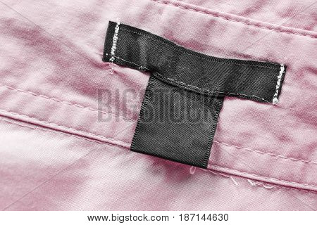 Blank black clothes label on pink cotton as a background