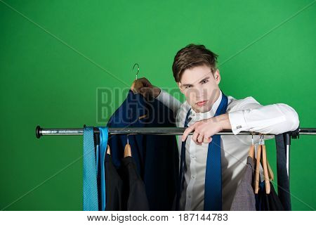 Man Dressed In Shirt, Stands Near Hanger With Clothes