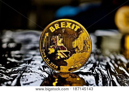 Gold brexit physical coin in black scene