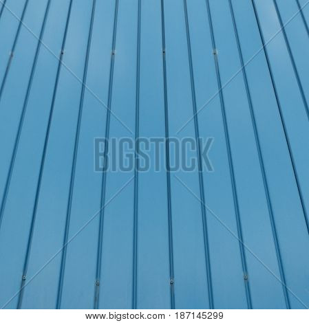 Blue goffered metal texture, corrugated steel surface with lines. Industrial background in perspective. With empty space for text.