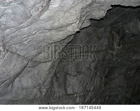 Cave entrance - rocky wall out into the darkness. Gray stone texture with cracks and roughness.
