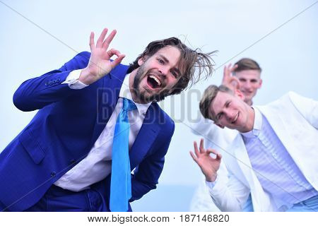 happy business team making ok gesture on light sky background for business teamwork concept