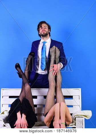 man or businessman in suit and sexy legs or woman girl in fashionable shoes and tights on white wooden bench on blue background love and relations power boss office romance sexual services