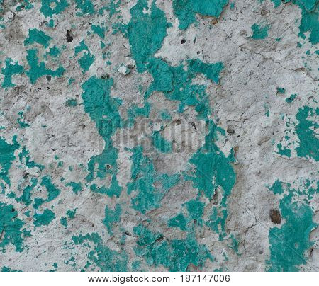 Green and gray plaster texture with lot of cracks and roughness. Abstract grunge background. Irregular structure.