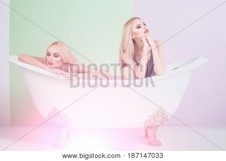 love and relations sexy women and pretty girls with blond long hair lying in white bath bathtub or tub. Young lesbian couple relaxing together. Homosexual love and LGBT
