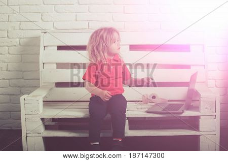 Little Kid Wearing Headphone Near Laptop On White Background