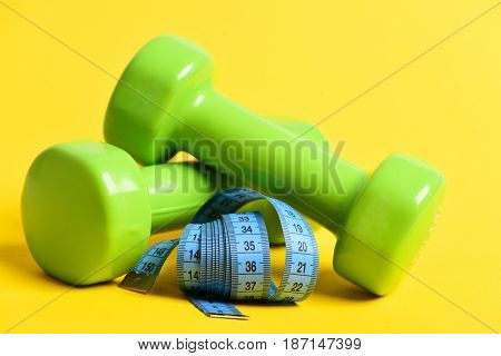 Fitness Body Concept With Dumbbells And Measuring Tape