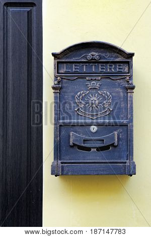 Metal mailbox in antique style hanging near the front door of the house on yellow wall