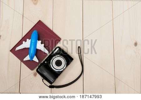 Camera with air plane and notebook for travel wooden table background. Top view with copy space.