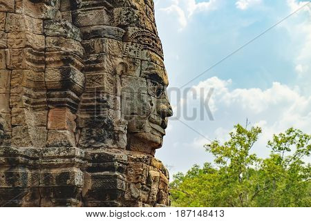 Smiling stone face of Prasat Bayon the central temple of Angkor Thom Complex, Siem Reap, Cambodia. Ancient Khmer temple is surrounded by tropical trees famous Cambodian landmark, World Heritage.