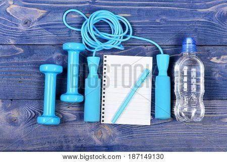 Water Bottle, Notebook, Skipping Rope And Dumbbells On Blue Vintage
