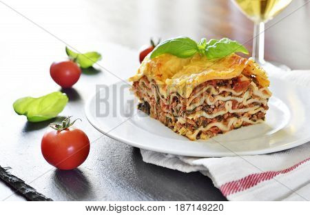 Fresh italian meat lasagne with cherry tomatoes. Italian pasta dish on a white plate.