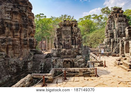 Siem Reap, Cambodia - February 2, 2016: Young tourist makes photo of Prasat Bayon the central temple of Angkor Thom Complex with smiling stone faces. Famous Cambodian landmark, World Heritage.