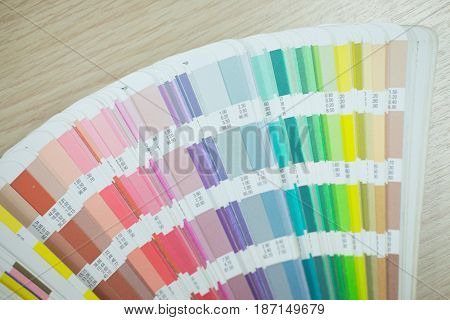 Pantone color palette guide on wooden board close up