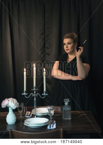 Woman Retro 1950S Style Standing With Cigarette At Dinner Table.