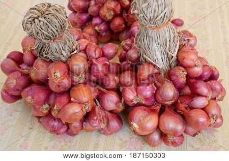 Red onions dry are tied together on table.