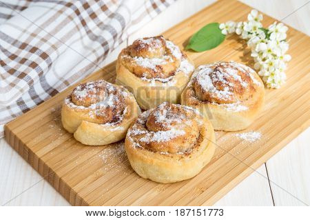Buns with cinnamon and powdered sugar on a light wooden table.