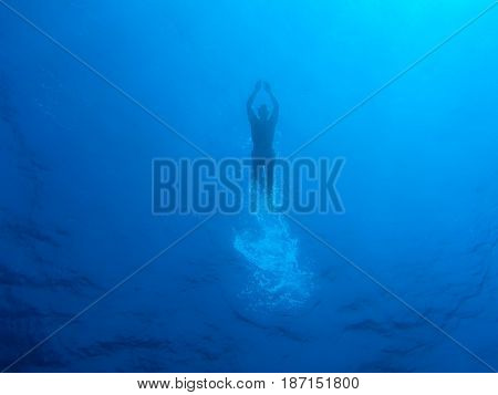 Egypt. Red sea. A person swims on the surface in fins. Shooting from under the water.
