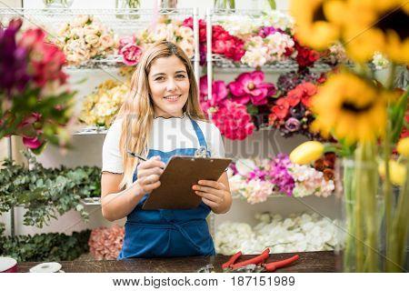 Florist Using A Checklist In Her Workshop