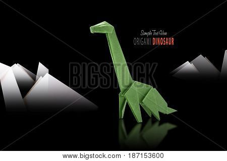 Isolated origami paper green dinosaur on black mountain background