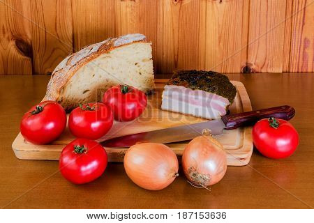 Ham tomatoes onion and bread on wooden cutting board. Selective focus