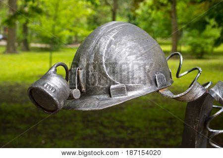 Donetsk Ukraine - May 09 2017: Miner's helmet forged figures forged from metal in the park