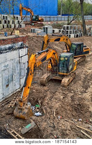 Yellow excavators digging the ground. Construction site