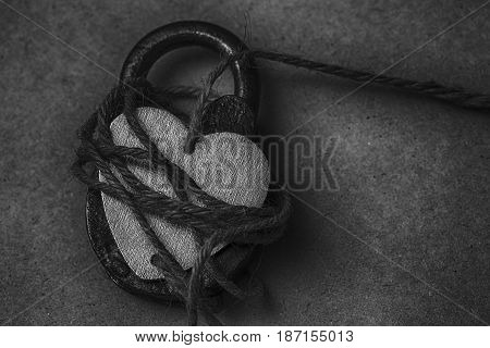 Heart on the lock. Conceptual photo of a symbolic heart with a rope tied to the hanging castle