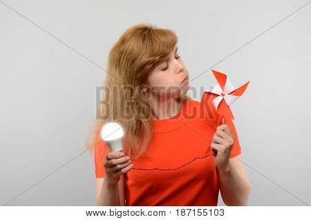 The Concept Of Renewable Energy. Woman With Led Light Bulb And Windmill