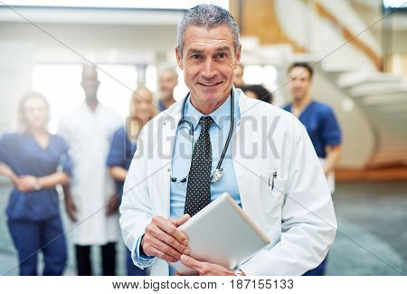 Cheerful Doctor With Tablet In Hospital In Front Of Team