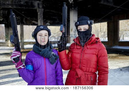 Girl and woman with gaming guns outdoor on winter day.