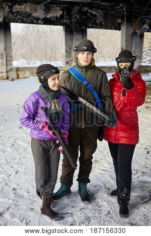 Girl, boy and woman with gaming guns outdoor on winter day.