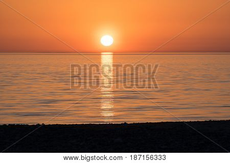 Bright orange sunset over the calm sea in calm weather