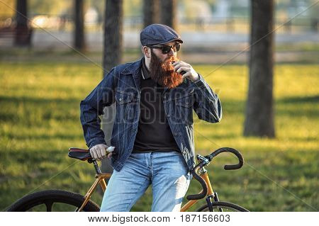 Vape in real life. Young man with gourgeous large beard and in sunglasses and in the cap having a rest and vaping an electronic cigarette near vintage fix bicycle after ride in the city park.