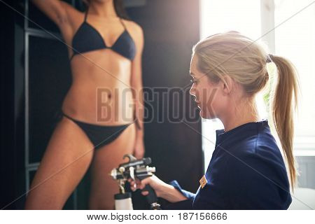 Cosmetologist Spraying Tan Bodypaint On Woman In Salon