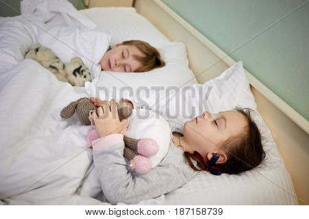Little girl and boy sleeping in bed with soft toys, focus on girl.