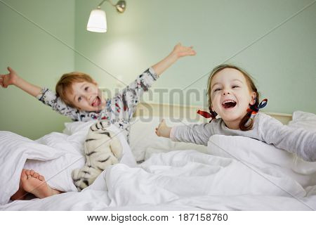 Smiling little girl and boy outstretched arms in bed with soft toys after awaking, focus on girl.