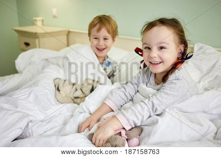 Smiling little girl and boy in bed with soft toys after awaking, focus on girl.