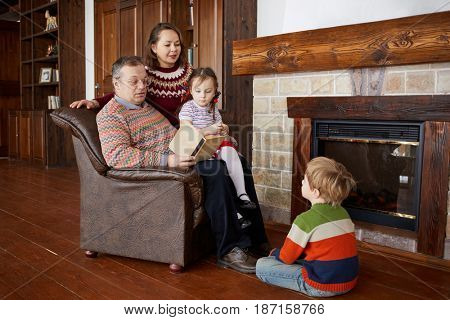 Father reads book aloud sitting in armchair near fireplace, mother and two children liten to him.