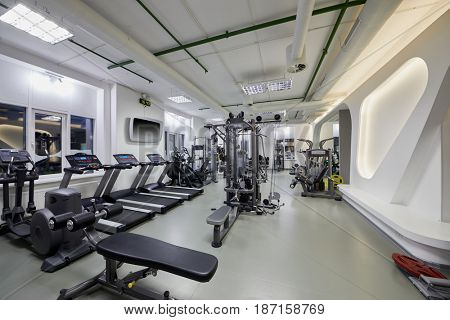 Modern gym room with plenty of fitness equipment.