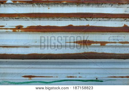 Old white metal fence with rusty spots and some green paint. Retro background - aged steel surface.