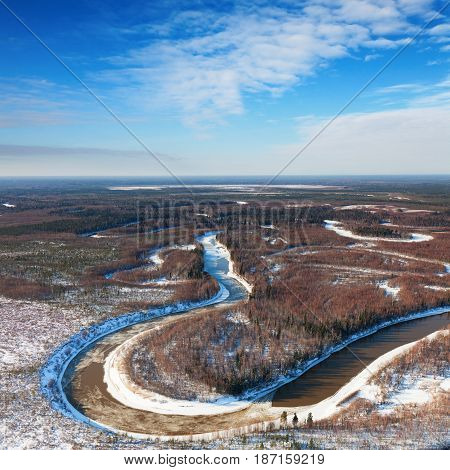 River in snow covered fir forest during cold winter day, aerial view.