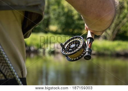 Rod with reel hunting trout. In the background the trout river Otava South Bohemia. Czech Republic.