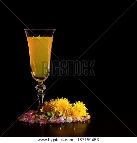 Wine from dandelions in a glass. Black background. Postcard