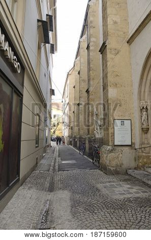 GRAZ, AUSTRIA - MARCH 20, 2017: Narrow alley next to the Parish church in the old city of Graz the capital of federal state of Styria Austria.